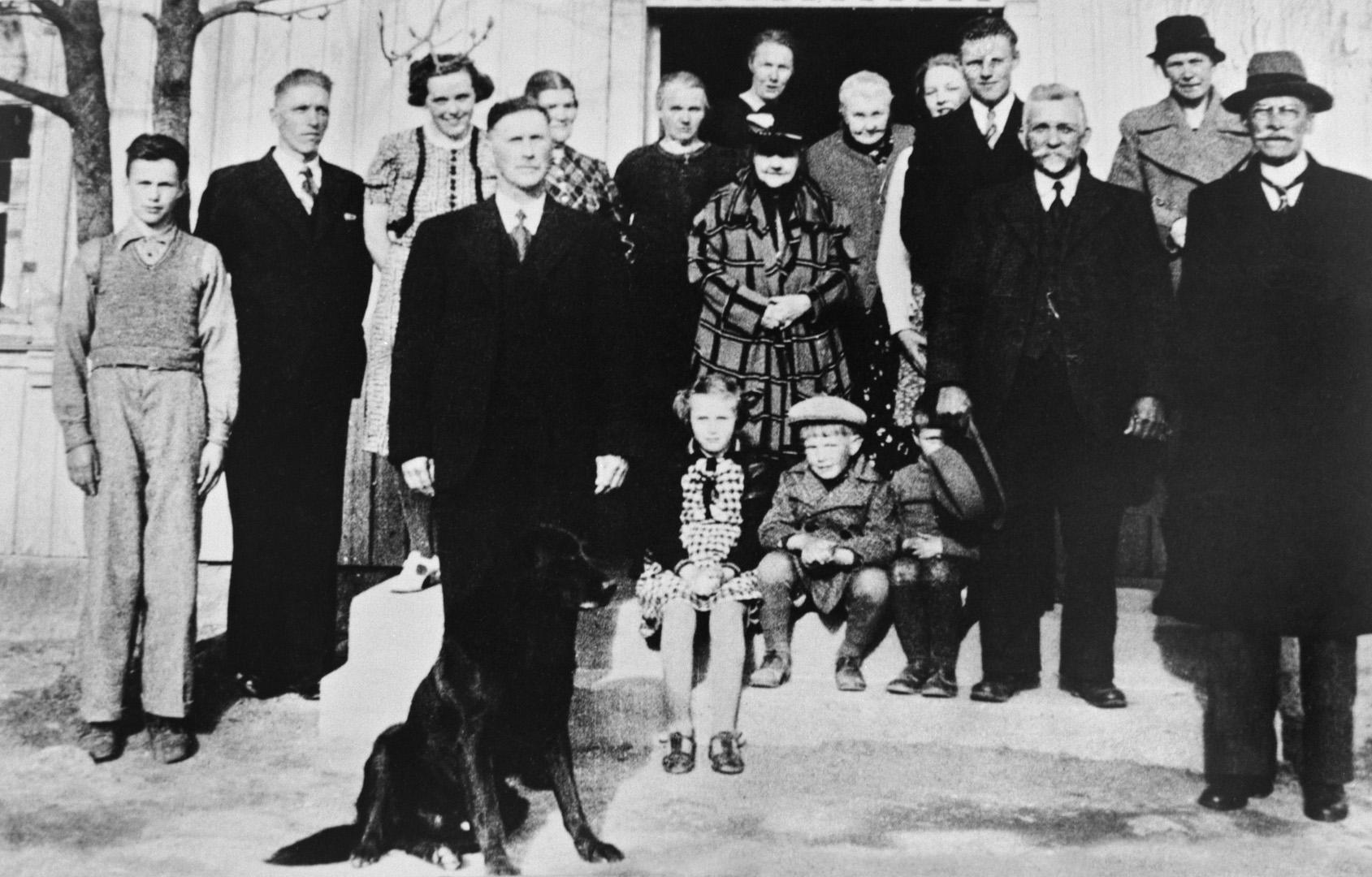 ØFB.1978-00547 Evakuerte i krigsdagene i april 1940 på gården Lunde i Varteig, nabokommune til Sarpsborg. Fra venstre nr. 2 og 3: Anders og Martha Sælid. Foran ved hunden: Erik Lunde, til høyre for ham: Elise Lunde. Med hatt i hånda: Rich. Snoppestad. I midten med mønstret kåpe: Fru Furuholmen, over henne datteren. Lengst til høyre Ingeniør Gunerius Furuholmen. Ellers: familien Kristiansen fra Sarpsborg. Fotograf ukjent / Østfold fylkes billedarkiv.