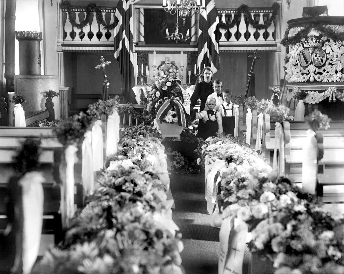 ØFB.CLA.UNR.00089 Fra begravelsen til gårdbruker Einar Molteberg, Ingedal kirke, Skjeberg i 1944. Ved kista står kona Augusta og deres tre sønner, Jens f. 1934 og Egil f.1937 og Ivar f. 1939. De bodde på gården Øiestad søndre i Skjeberg. Einar var en av femti norske politiske fanger som ble sendt fra Norge til konsentrasjonsleir i Tyskland med det tyske troppe- og fangetransport-skipet D/S Westphalen. Skipet forliste 8.9. 1944 utenfor Marstrand i Sverige (torpedering eller mine), og bare fem av de norske fangene overlevde. Foto: Christian E. Larsen / Østfold fylkes billedarkiv. Mannen Einar Ludvik Joachim Molteberg f. 1906, d. 1944, døde ved Westfalens forlis 8.september 1944. På gravstøtta: Død ved Westfalens forlis 8-9-1944 01 11 03 Alltid i kamp for Norges sak, selv bak gitter og lås du stred, inntil det redselens brak, trakk deg i bølgene ned