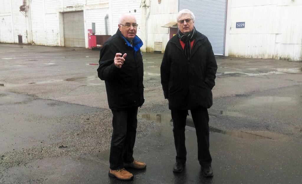 To menn utenfor gammel fabrikkbygning