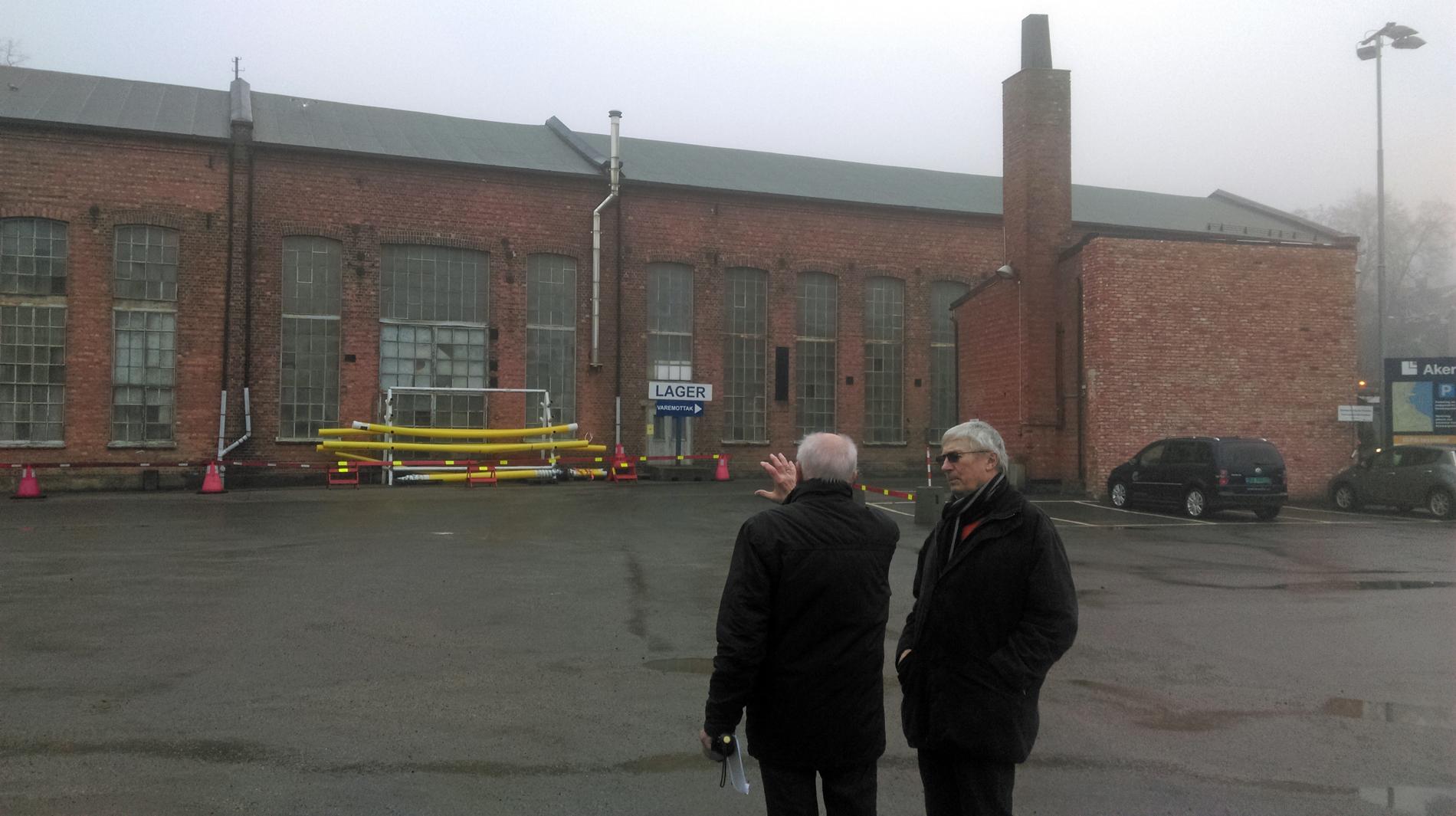 To menn i samtale foran verkstedbygningen