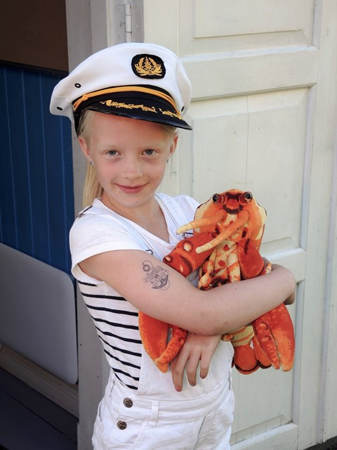 Helle med kapteinslue, tatovering og hummeren Harald på Kystmuseet.Foto Pål Bugge.