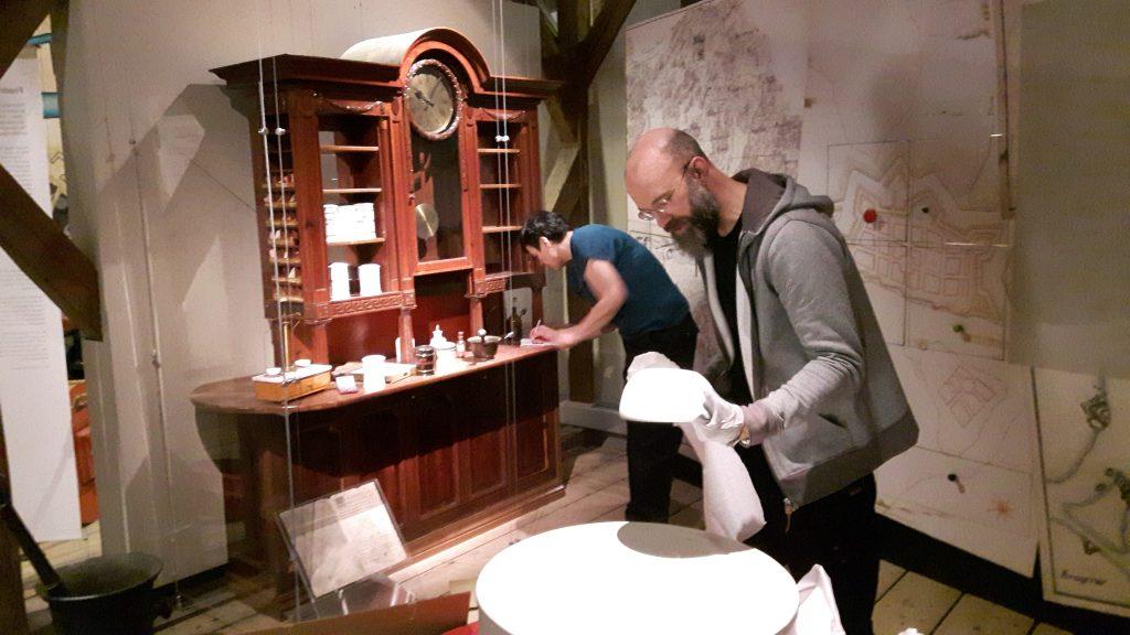 Gjenstandene fra gammel byhistorisk utstilling pakkes forsiktig ned. Foto: Christine Lande
