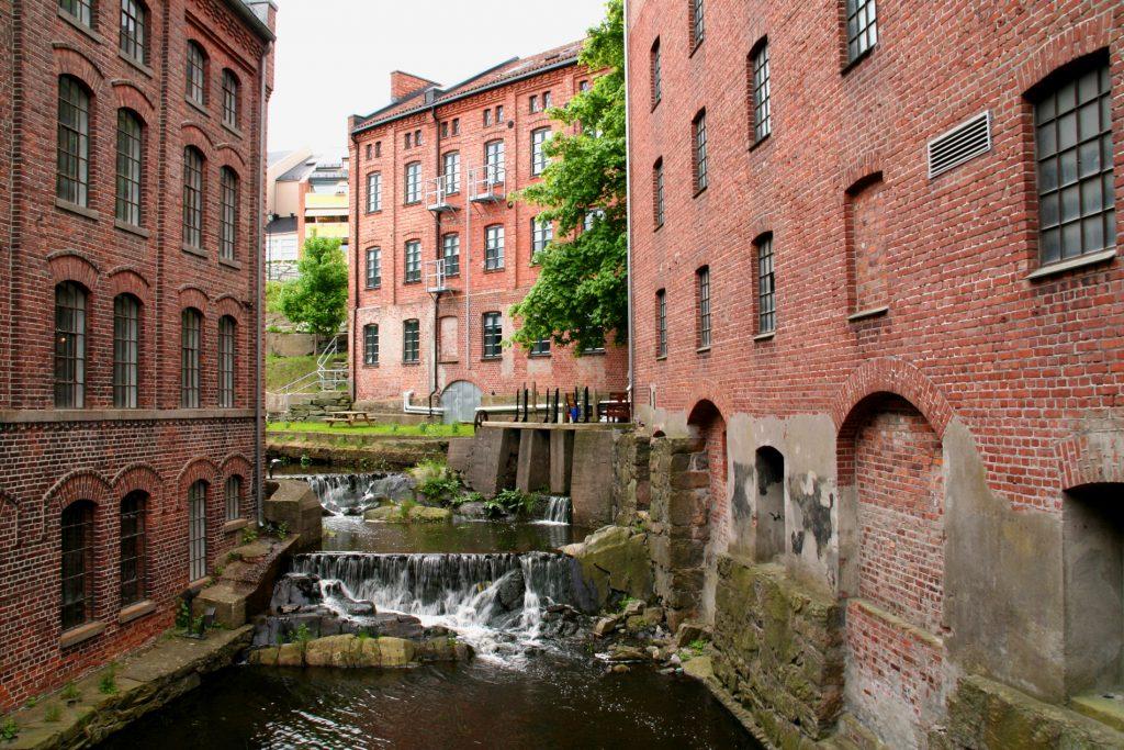 Gamle teglstensbygninger på begge sider av en elv.