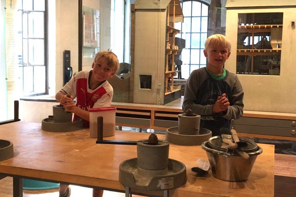 Laurits Strøm-Nielsen på 8 år (t.v.) og Christian Haugland på 9 år (t.h.) maler sitt eget mel og lærer litt lokal historie i samme slengen. Foto: Weronica Melbø-Jørgensen / Moss by- og industrimuseum