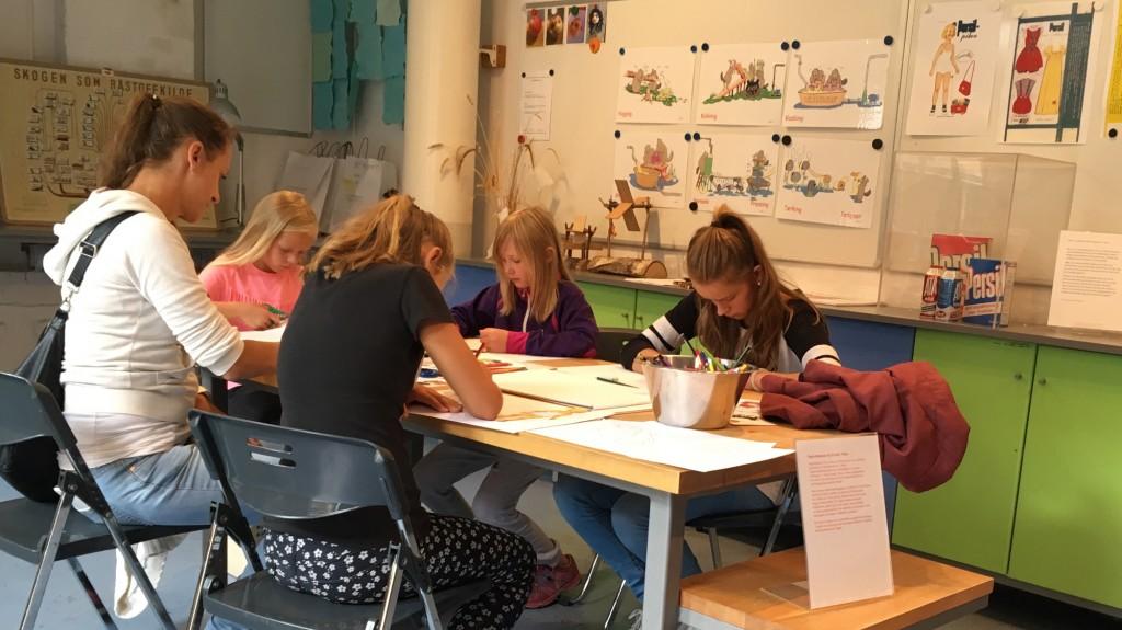 Fem jenter som lager papirdukker og klær