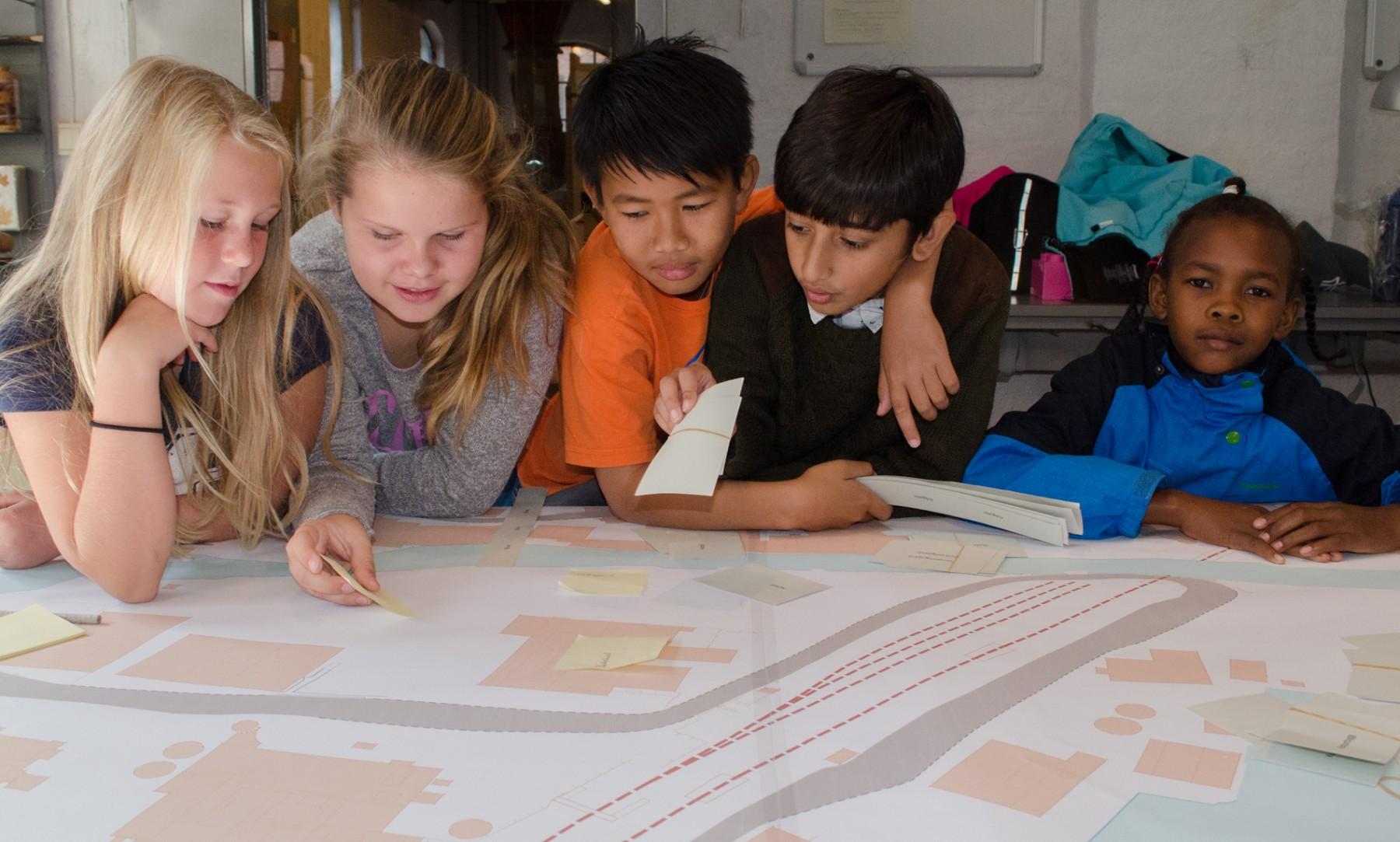 Fem barn lent over et stort kart over Verket Moss
