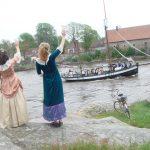 Flotte 1700-talls damer vinker til sjømennene på Anna Minde, fra Isegran. Foto Turid Alstad Hop.
