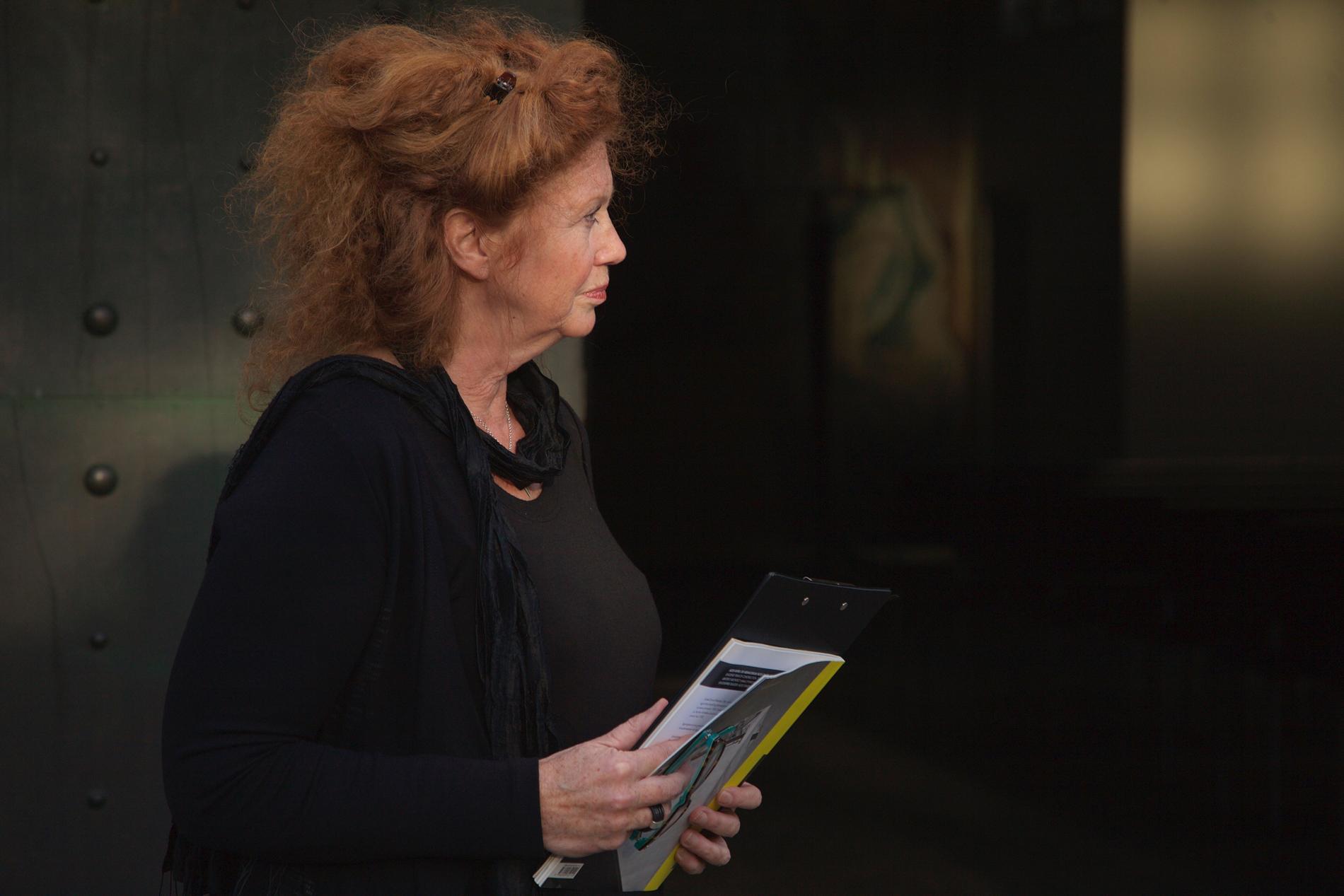 Torsobilde av kvinne med rødt hår og sort drakt.